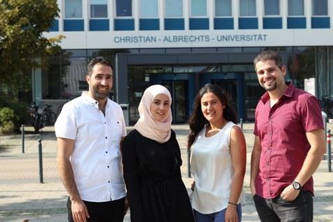 Vier Studierende vor dem Universitätsgebäude